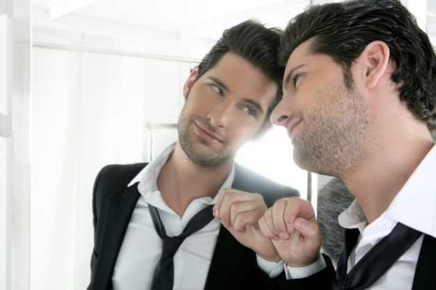 Portrayal of narcissistic young man looking in a mirror (stock image). Scientists have investigated whether narcissists can elicit empathy for another person's suffering.